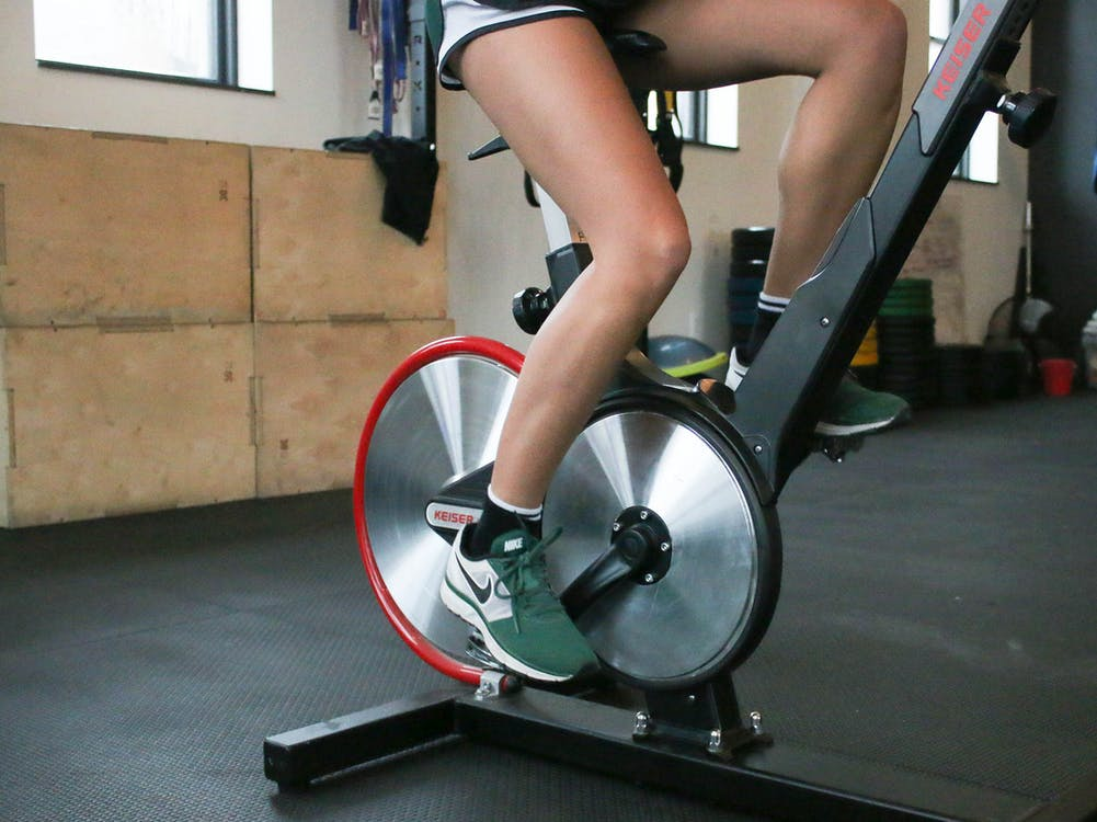 Person exercising on cycling machine in gym