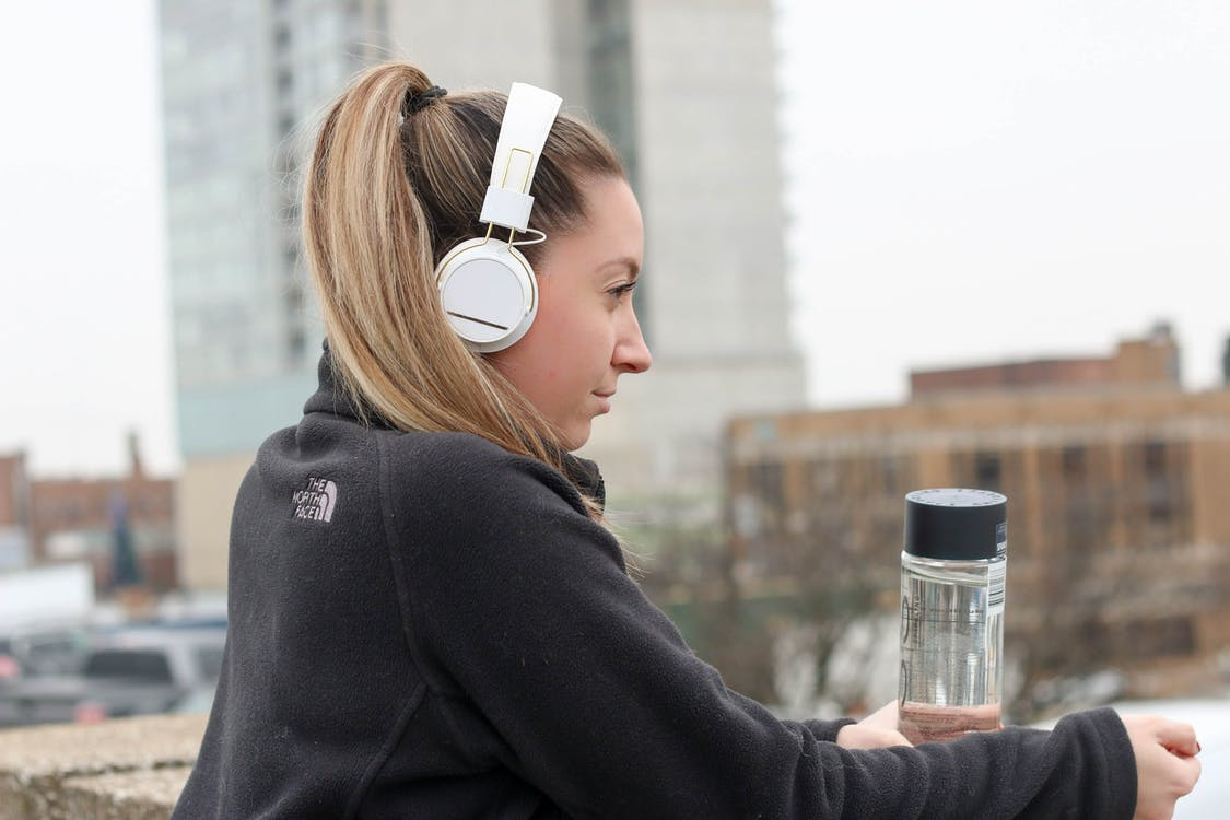 Woman Wearing Black Jacket With White Headphones