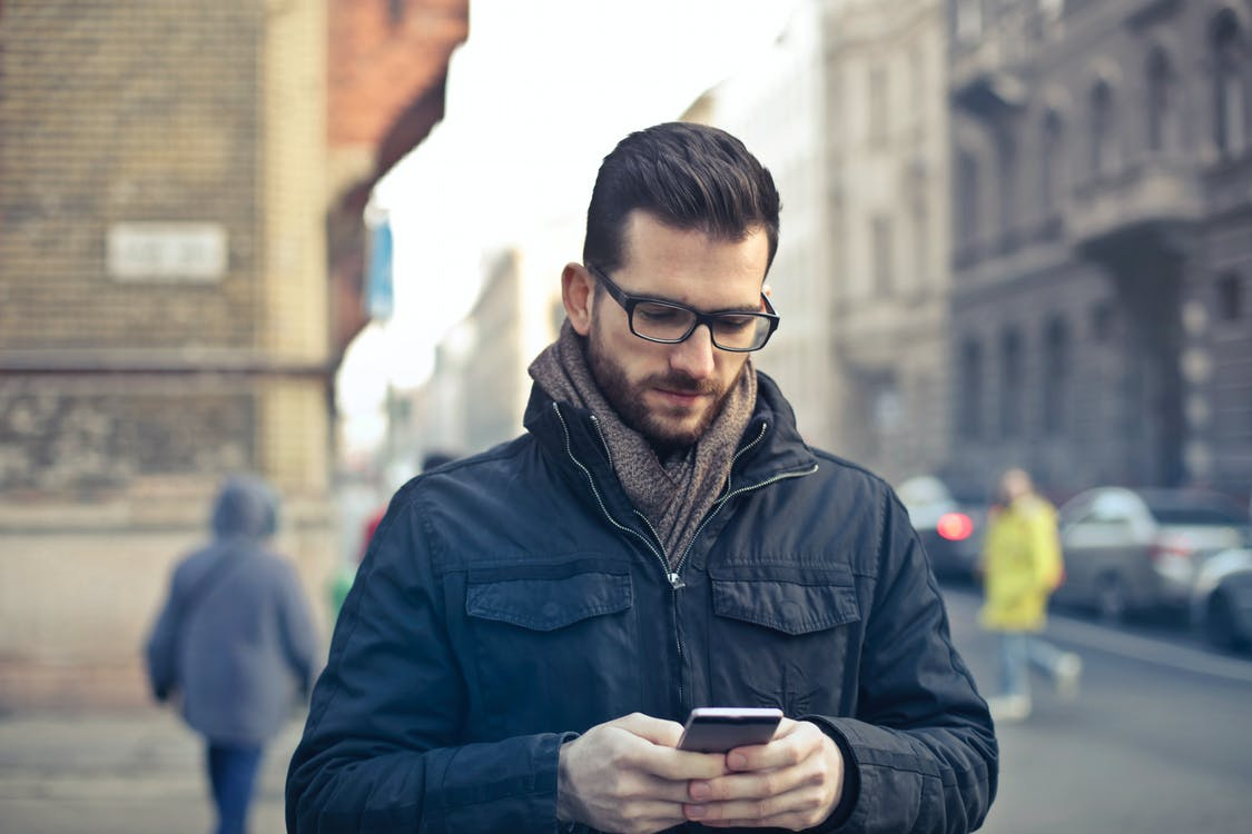 Man Wearing Black Zip Jacket Holding Smartphone Surrounded by Grey Concrete Buildings