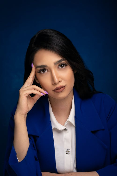 Confident young ethnic female in blouse and blue jacket leaning on hand while looking at camera