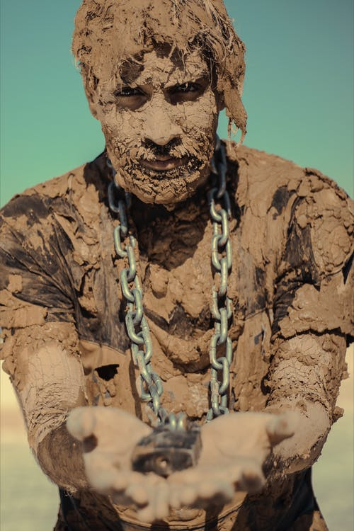Man with chain on neck covered with clay
