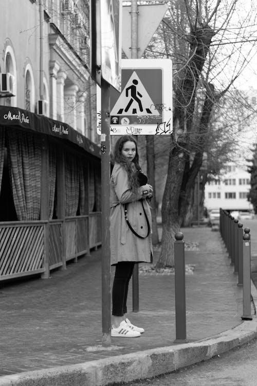 Woman Standing on City Sidewalk  Near the Street Sign