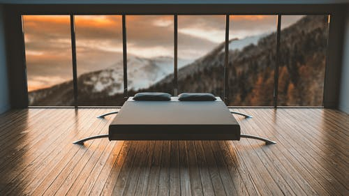 Black Mattress in Front of a Large Window Behind a Mountain
