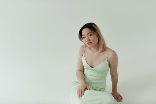 Beautiful Woman in a Light Green Dress Sitting in a Studio while Looking at the Camera