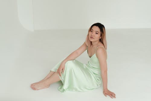 Beautiful Woman in a Light Green Dress Sitting on the Floor while Looking at the Camera