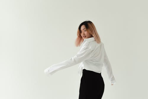Photo of a Beautiful Woman in a White Dress Shirt Looking Back