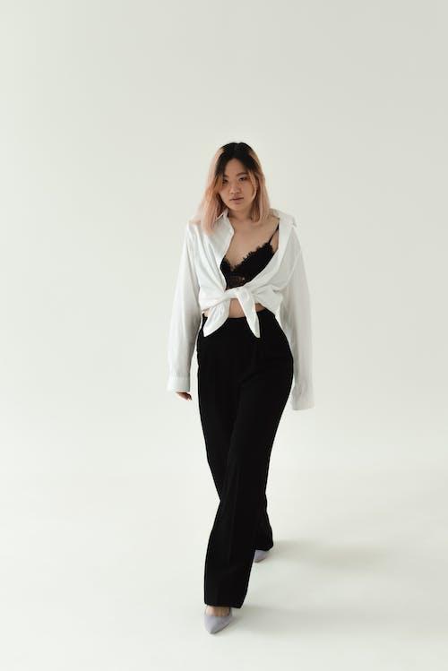Beautiful Woman in Black Pants Walking in a Studio