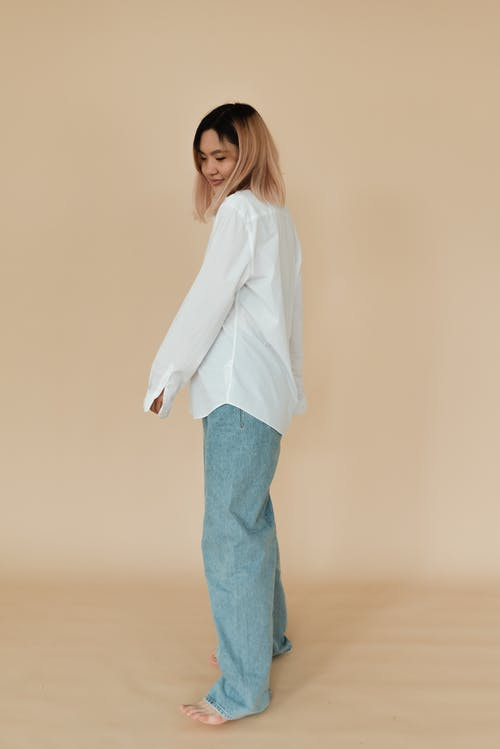 A Pretty Woman in White Long Sleeves and Denim Pants