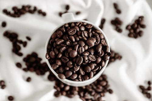 Top view of coffee beans in cup near scattered grains on crumpled white cloth