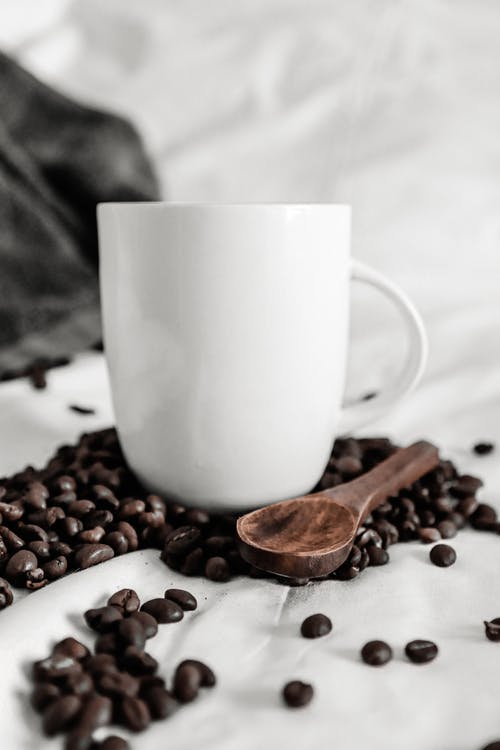 Coffee beans scattered on white cloth near cup