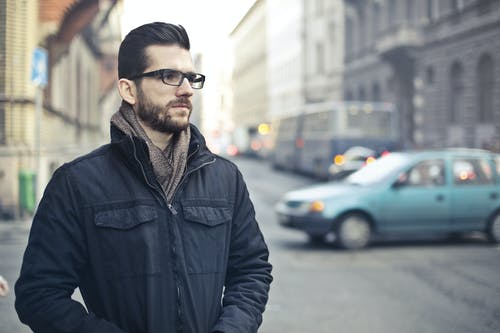 Man Wearing Black Zip-up Jacket Standing on the Street