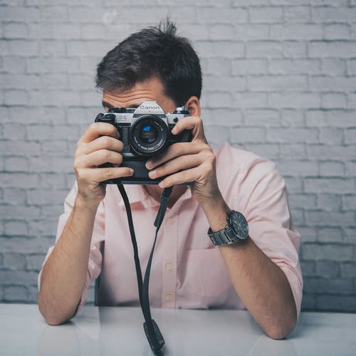 Anonymous male photographer sitting at table and taking photo with vintage photo camera