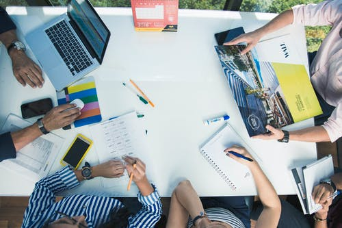 From above of crop unrecognizable coworkers gathering around table with laptop and papers while working together in office