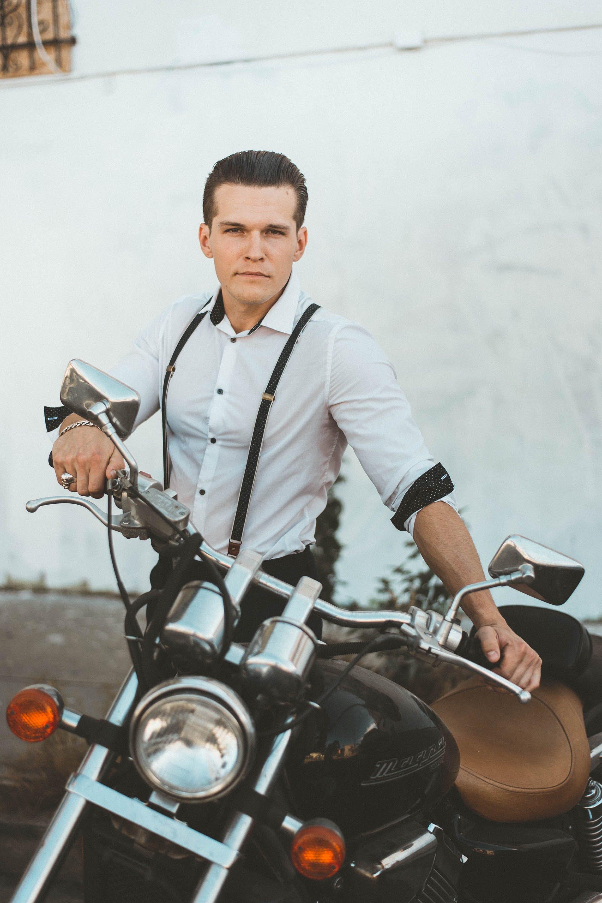 Man in White Dress Shirt Standing Beside Black Motorcycle