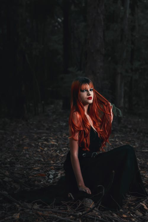 Woman in Red Hair and Black Dress Sitting on Tree Trunk in Dark Forest