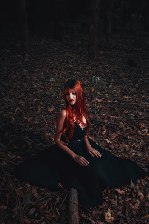 Woman in Red Hair and Black Dress Sitting in Forest at Night
