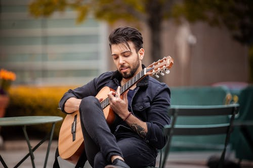 Selective Focus Photo of a Man Playing a Brown Acoustic Guitar