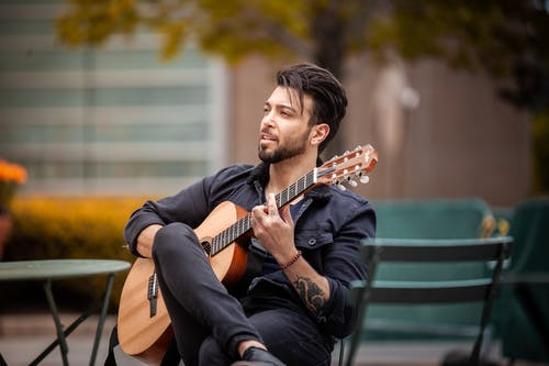 Man with a Beard Playing a Brown Acoustic Guitar