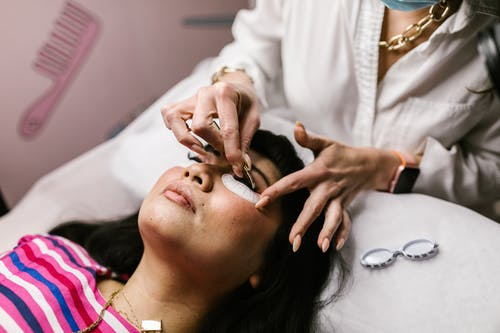A Woman Putting on Eye Lashes