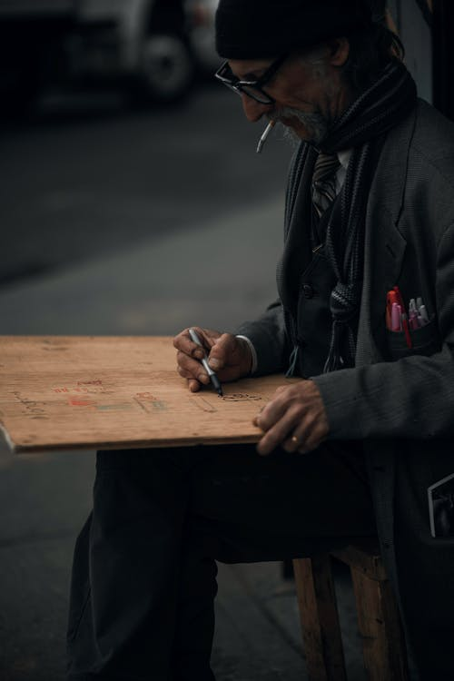Man in Black Jacket Holding Brown Wooden Plank