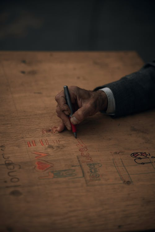 Person Writing on Brown Wooden Table