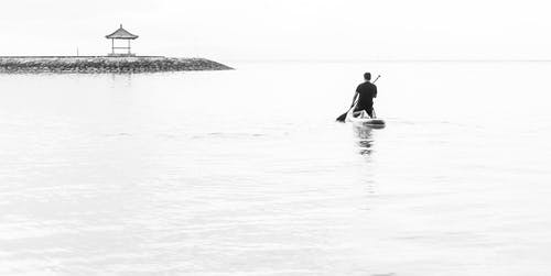 Man in Black Wet Suit Riding on White Surfboard on Sea