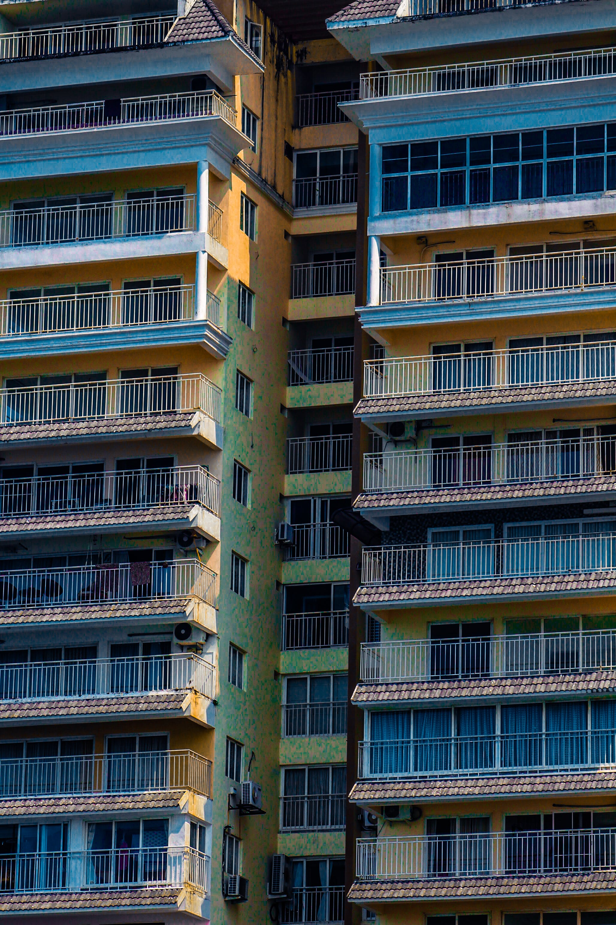 Free stock photo of apartment buildings, artificial flowers, bright colours, facade