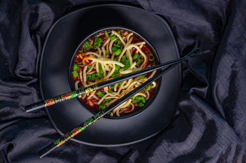Top view of black bowl with Asian soup with noodle and green onion served with bamboo chopsticks on black tablecloth