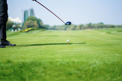 Anonymous golf player preparing to hit ball