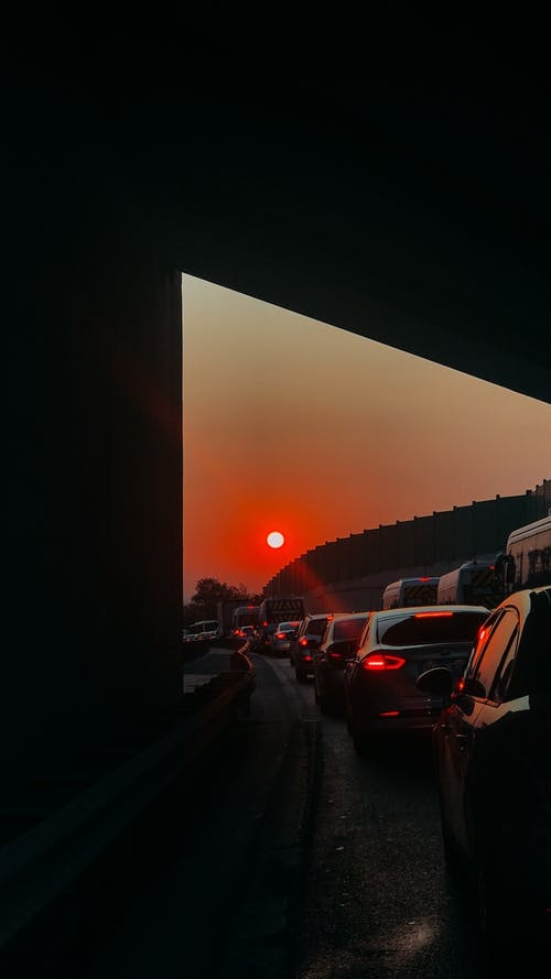 Through from tunnel of many modern automobiles driving in traffic jam at sundown time against bright sun shining on sky