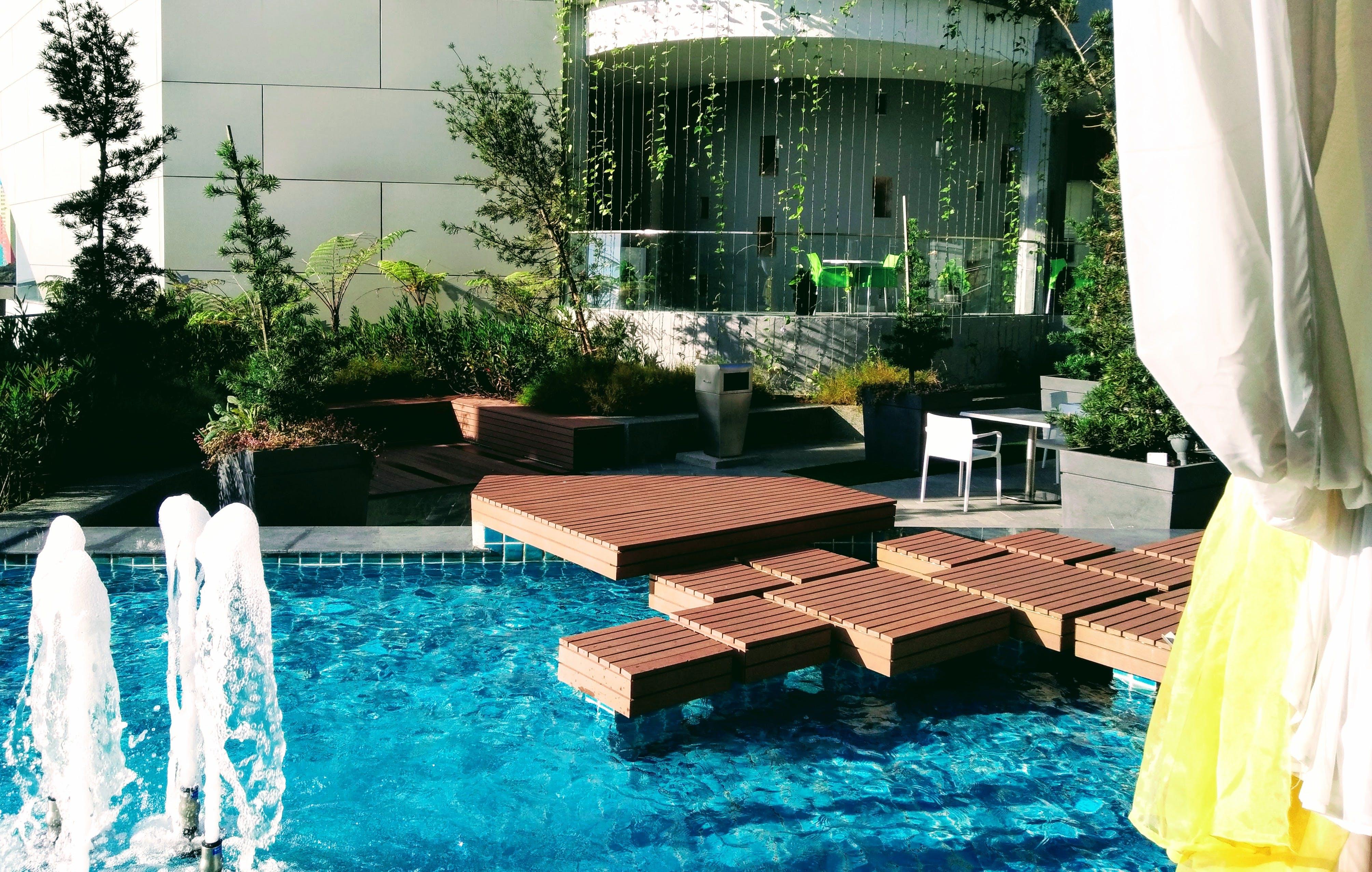 Безкоштовне стокове фото на тему «архітектура, біля басейну, вода, заводи»