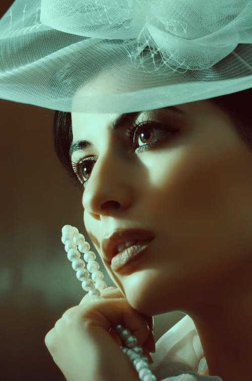 Woman in hat with bijouterie looking away pensively
