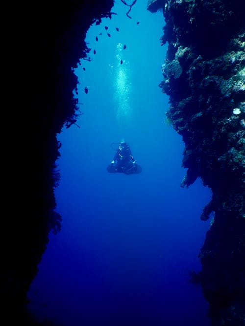 Unrecognizable person floating undersea with crossed legs near corals