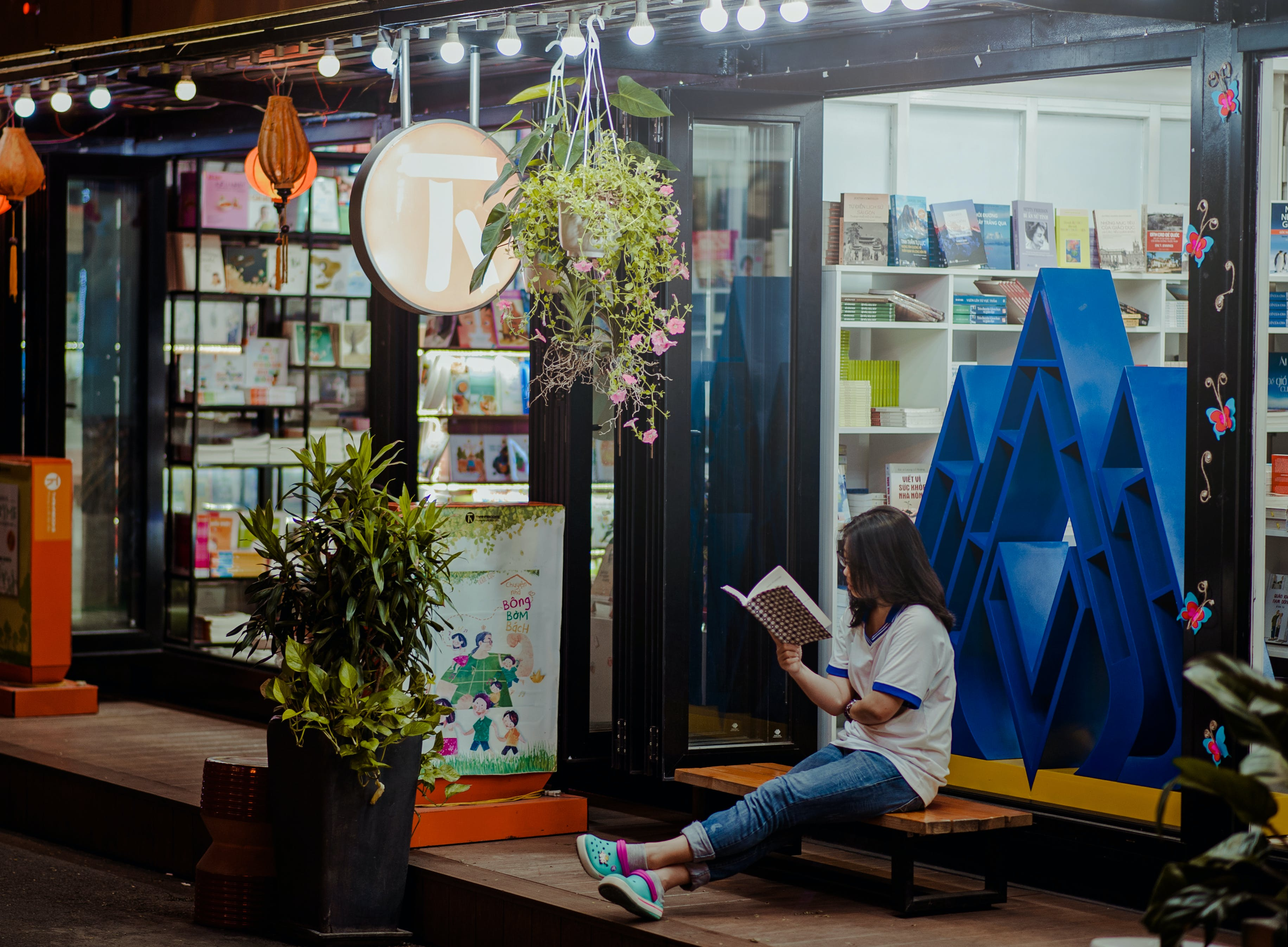Woman Sitting Down On Bench And Reading Infront of Store