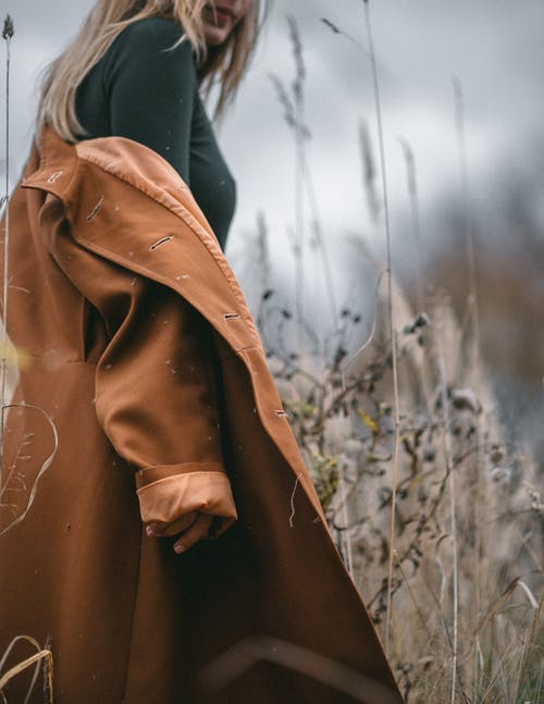 Stylish woman in trendy coat in field with dry grass