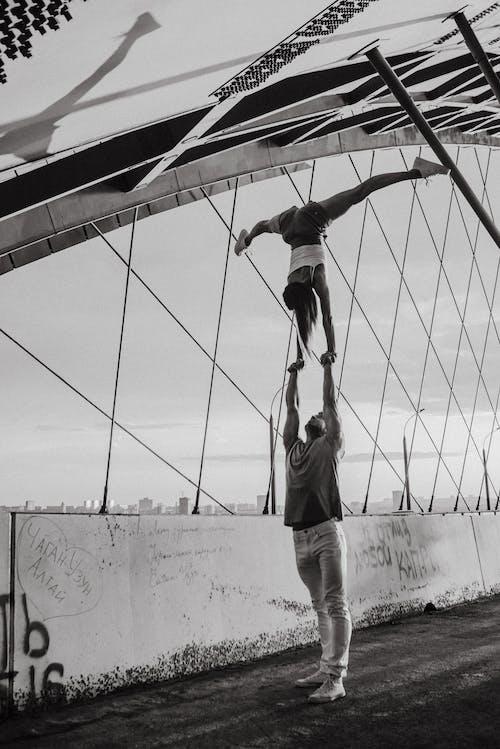 Gymnastic woman and man doing trick on bridge