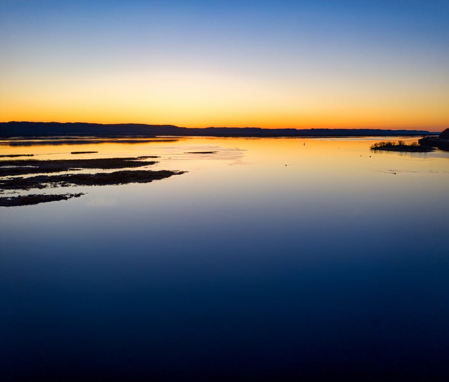 Calm Water Under Blue Sky during Sunset