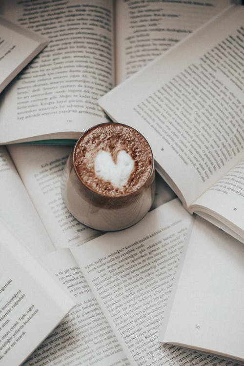 Cup of cappuccino placed on pile of opened books