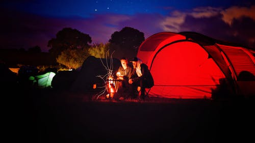Man and Woman Sitting Beside Bonfire during Nigh Time