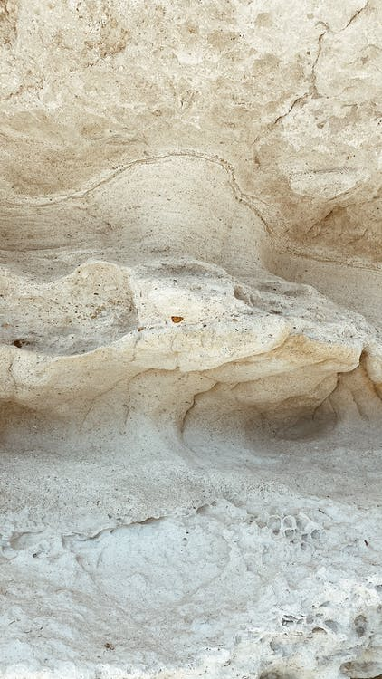 Closeup of abstract background of textured rough surface of rocky cliff on sunny day