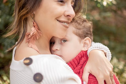 Close-Up Photo of a Child Looking at the Camera while being Hugged by Her Mother