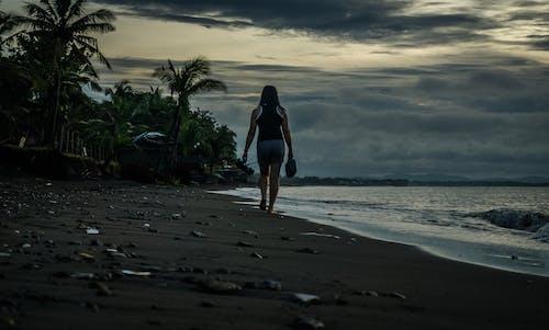 Kostenloses Stock Foto zu barfuß, bewölkt, meeresküste