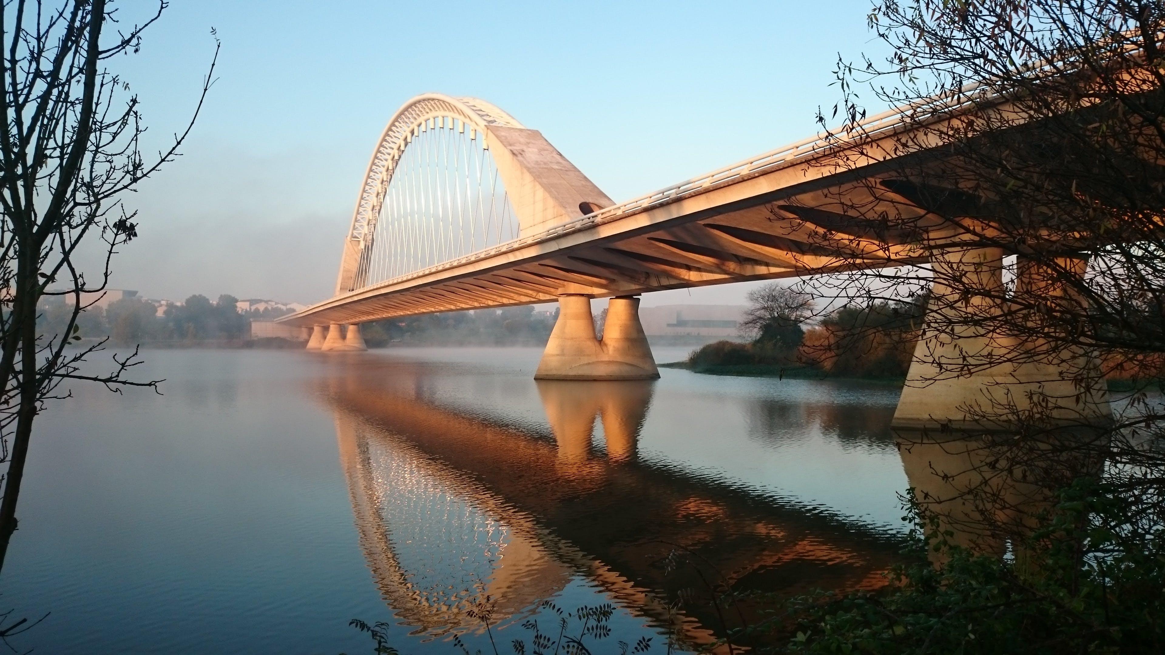 Grey Concrete Bridge Above Water Under Blue Sky