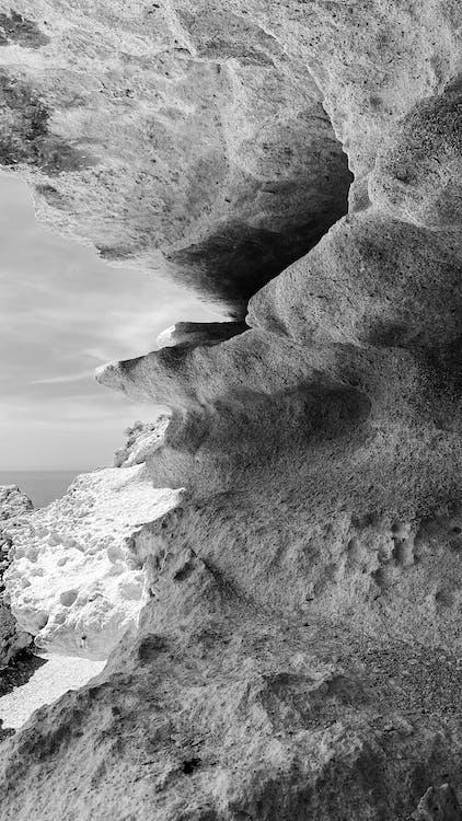 Rocky cave on seashore on sunny day