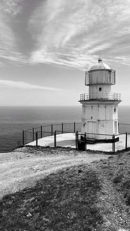 Black and white of old Meganom Lighthouse located on rocky cape above wavy sea against cloudy sky