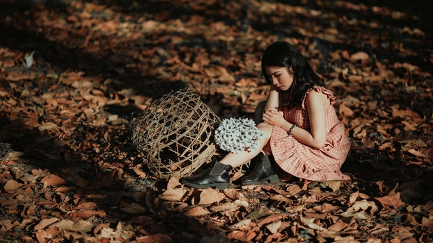 Woman Wearing Red Dress Sitting on Brown Ground With Woven Brown Basket