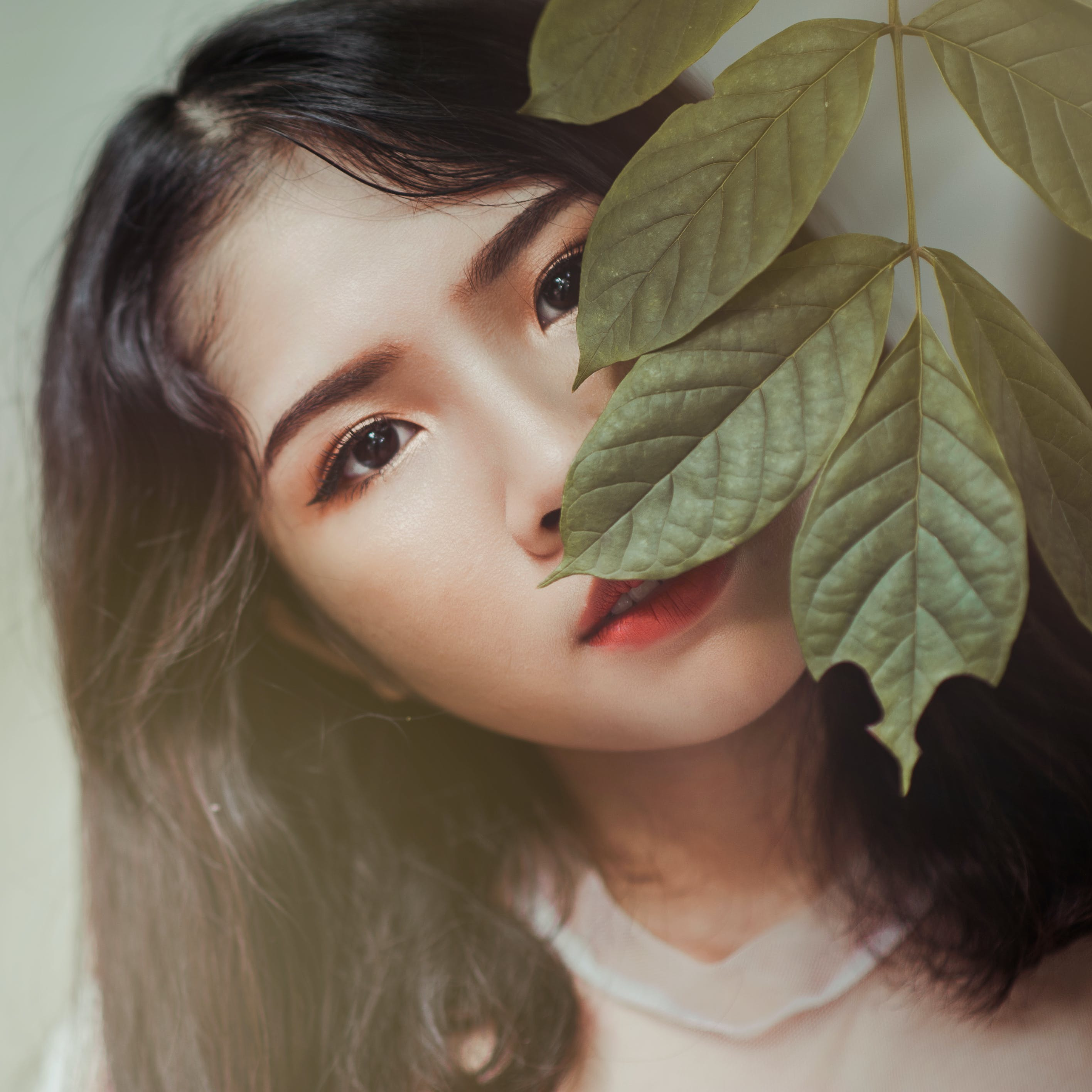 Photography of Brown Haired Woman Near Green Leaves