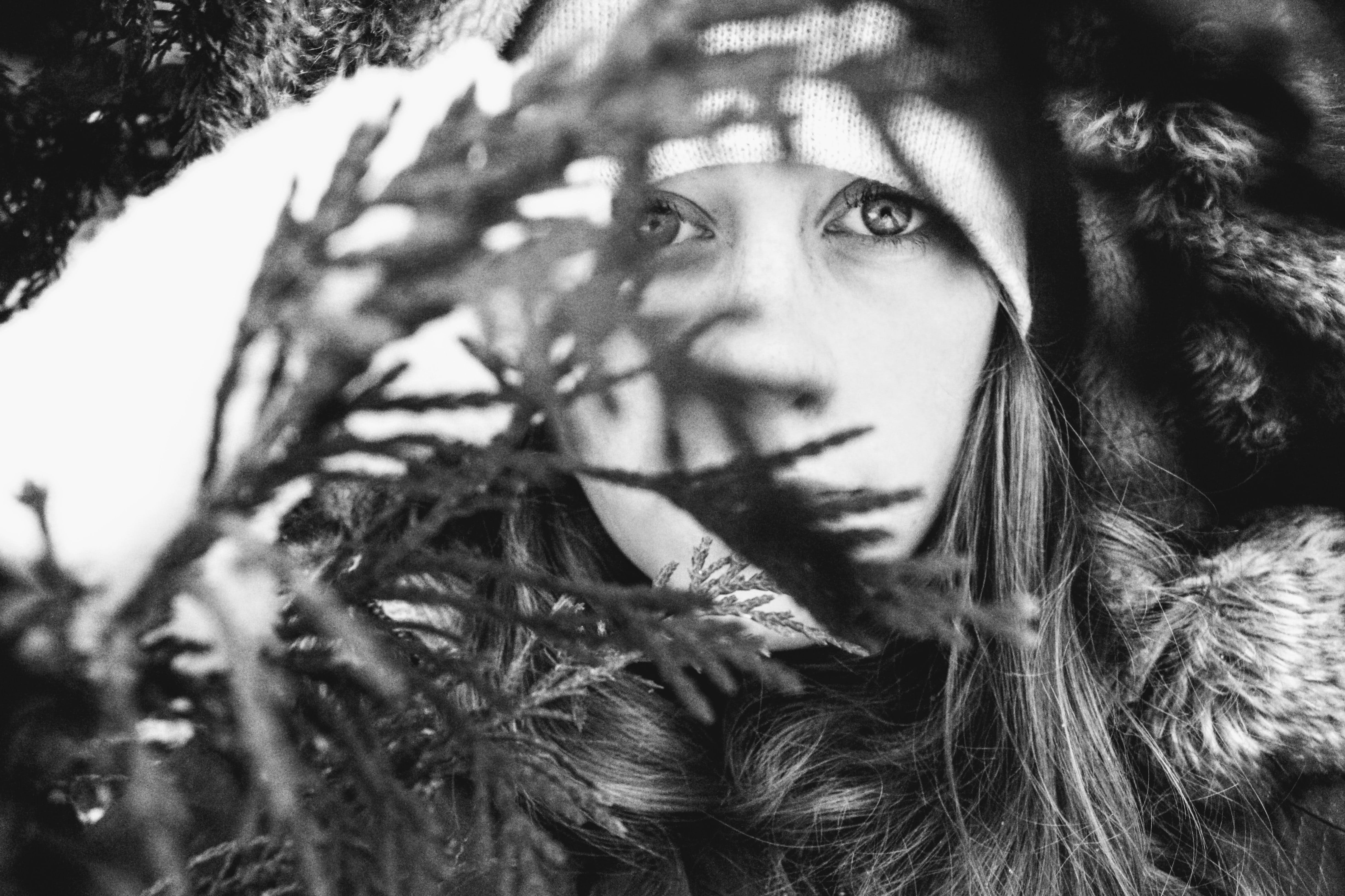 Grayscale Photo Of Woman Behind Leaves