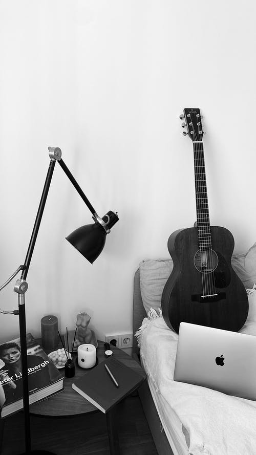 Greyscale Photo of Acoustic Guitar on Guitar Stand