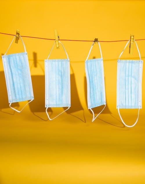 Kostenloses Stock Foto zu gehängt, gelbem hintergrund, gesichtsmasken